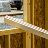 stack of wood stud planks at construction site resting on window opening