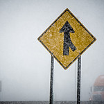 merge sign barely seen through winter storm