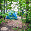 tent in forest on campground by the lake