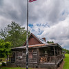 old log cabin and american flag