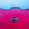 red sports car wet from rain drops