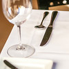 elegant dinner table set with knife fork and wine glass